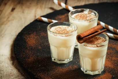 Traditional winter eggnog with milk, rum and cinnamon, sprinkle with grated nutmeg, selective focus